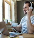 Smiling man listening to headphones and holding a cup of coffee at coffee shop