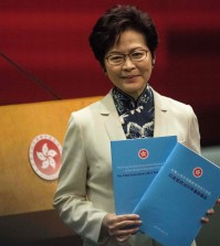 Hong Kong's Chief Executive Carrie Lam poses with copies of her first policy address as she arrives for a press conference at the Legislative Council in Hong Kong on October 11, 2017.  Hong Kongers have a duty to stand up for China over threats to its sovereignty, the territory's leader Carrie Lam said on October 11, months after Beijing warned against any challenge to its control over the semi-autonomous city. / AFP PHOTO / Anthony WALLACE