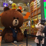 A woman poses for a photo with a giant bear at a 'Line' store in a shopping district of Seoul on March 28, 2017. Asia's fourth-largest economy grew slightly more than previously thought in each of the past two years, South Korean authorities said on March 28. / AFP PHOTO / JUNG Yeon-Je