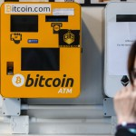A woman uses her phone as she walks past an ATM machine for digital currency Bitcoin in Hong Kong on December 18, 2017. Bitcoin has soared in recent weeks, breaking numerous records, and has risen more than 20-fold since the start of 2017. / AFP PHOTO / Anthony WALLACE