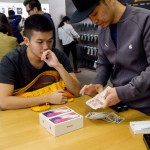 An employee (R) counts cash at an Apple store as a customer buys two 10th anniversary iPhone X's in Hong Kong on November 3, 2017. Apple profits soared by a fifth as its flagship iPhone X hit stores in Asia on November 3, with the company predicting bumper sales despite its eye-watering price tag. In Hong Kong, buyers who had pre-ordered the phone online queued to pick up their new purchases, saying they were willing to pay for what they saw as a landmark model. / AFP PHOTO / ANTHONY WALLACE